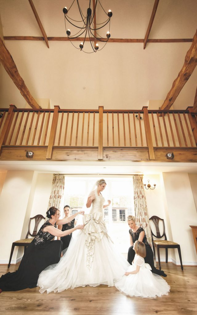 bride being helped into wedding dress by flower girl