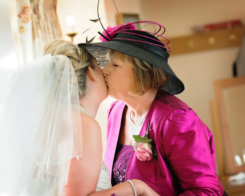 mother. of the bride kisses bride