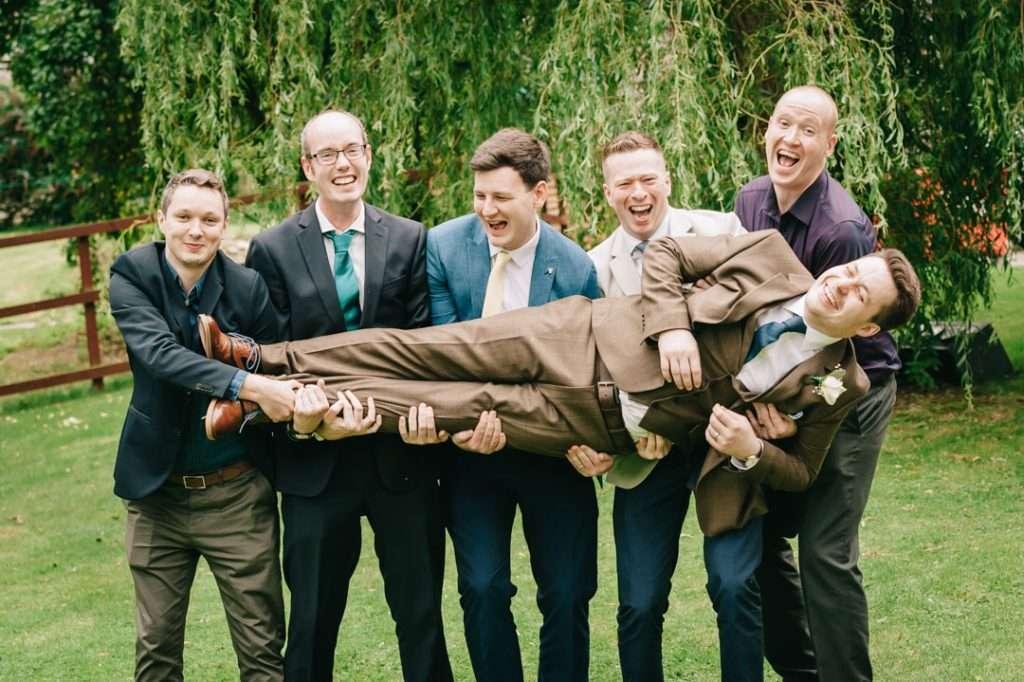 groom being held up by bestman funny