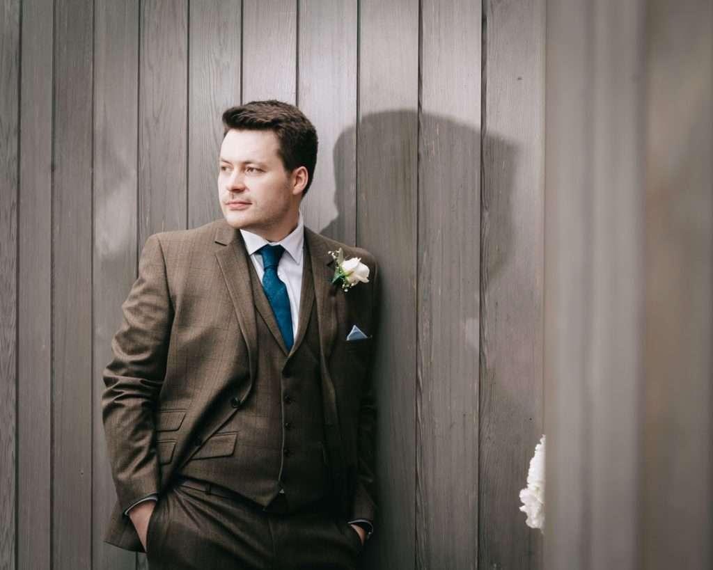 groom posing outside eco house