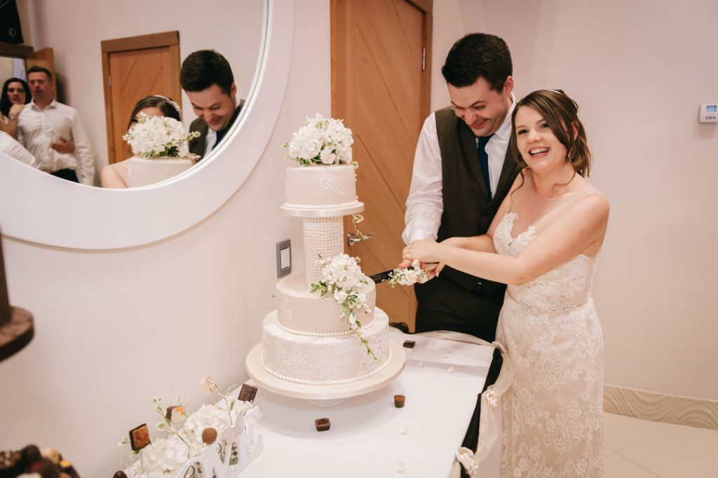 man and woman cutting wedding cake