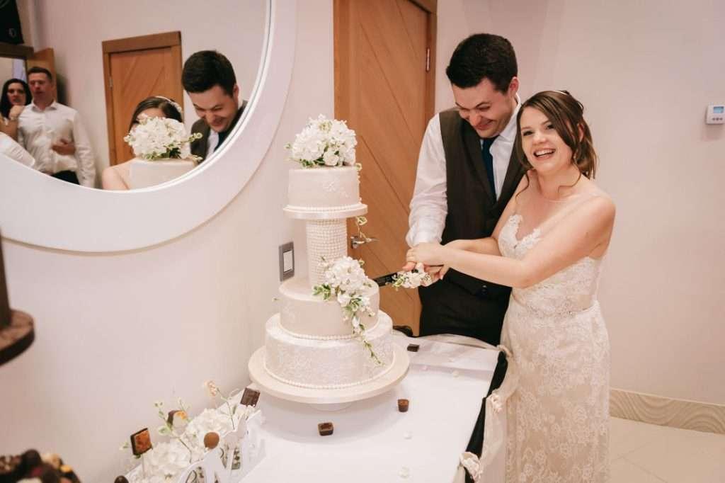 man and woman cutting wedding cake